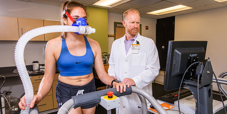 Scott Rector, PhD collecting data on research participant who is wearing a mask and walking on a treadmill